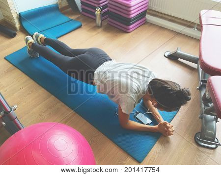 Asian Young Woman Exercising Plank Pose in the Gym. Fitness Lifestyle Photo of Active Girl Who Wants to Lose Weight and Stay Fit. Russia.