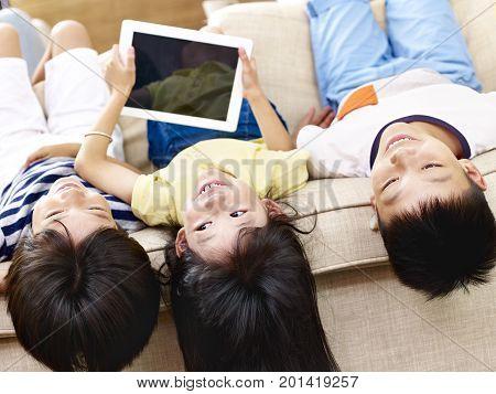 three asian children having fun lying upside down on couch.