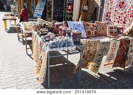 BUKHARA UZBEKISTAN - OCTOBER 19 2016: Uzbek souvenirs. Female saleswoman sells handicrafts on the streets of Bukhara