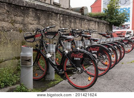 Galway Ireland - August 3 2017: Locked up row of black and red public bikes for rent with Coca-Cola Zero sponsoring on the back wheel.