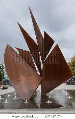 Galway Ireland - August 3 2017: Closeup of Quincentennial Fountain at Eyre Square shows rusty iron plates resembling sails standing in pool. Square with trees flowers bikes and people.