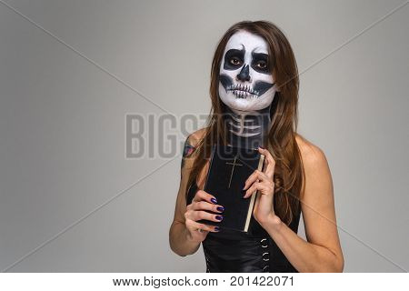 Portrait of woman with halloween skeleton makeup holding Holy Bible over gray background.