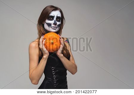 Woman with scary Halloween skeleton makeup holding pumpkin over gray background
