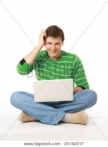 A puzzled young man sitting on the floor with a laptop