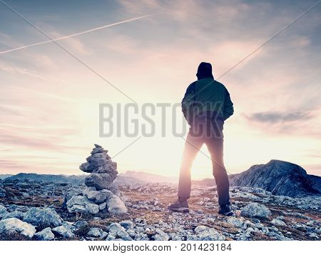 Tourist Guide At Stocked Stones On Alps Peak. Strong Hiker Enjoy Sunset In   Alpine Mountain.