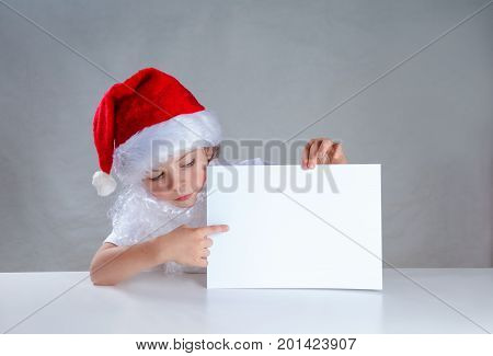 Little Santa Peeping From Behind A White Envelope And Looks At Him. He Is Sitting At A White Table.