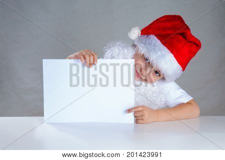 Little Santa Holding A White Envelope, Smiling. Sitting Behind A White Table Looking At The Camera.