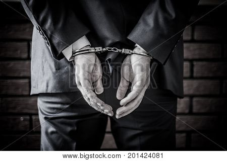 Businessman And His Hands On The Back Handcuffed Because Of Crime And Corruption In Business World.