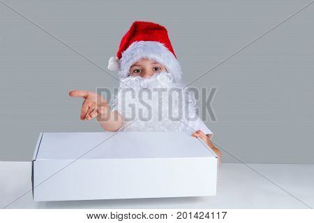 Little Santa Claus Holding In His Left Hand A White Box, Right Hand Pointing To The Camera By Turnin