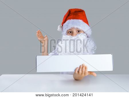 Little Santa Claus Holding In His Left Hand A White Box, Right Hand Held Up. He Is Sitting At A Whit