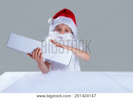 Little Santa Claus Wrapped His Arms Around The White Box. He Looks Into The Camera. Gray Background.