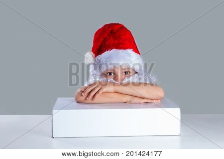 Little Santa Claus Put His Head On His Folded Arms On The White Box. He Is Sitting At A White Table.