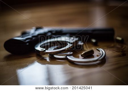 Police Equipment Handcuffs And Black Pistol On The Wooden Background. Fighting Against Violent Crimi