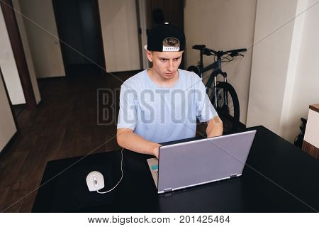 A serious young man looks at the laptop while sitting at the table in his room