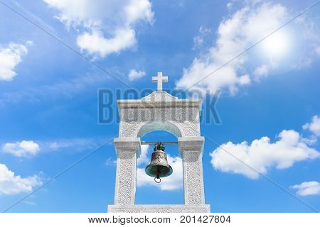 Close-up of a beautiful white bell tower in front of a Sun. View on a beautiful white Church on a sunny Day.