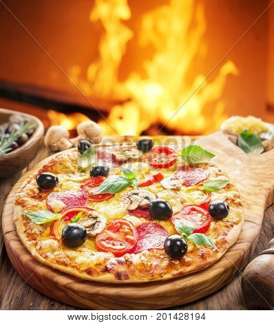 Pizza. Wood-fired oven on the background.