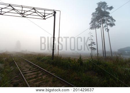 Gloomy railway in the fog in morning