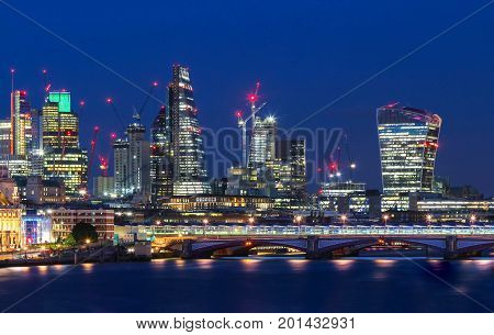 View of London's city hall and modern skyscrapers at night, London, United Kingdom.