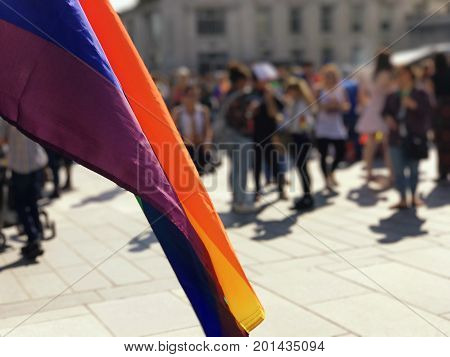 Rainbow flag with a blurred background showing people celebrating equality pride.