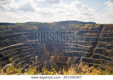 Big Abandoned opencast mining quarry against cloud sky.