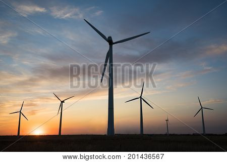 Power generators of windmills at sunset of the day.