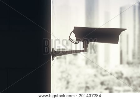 Side view of backlit CCTV camera on blurry city background. System concept. 3D Rendering