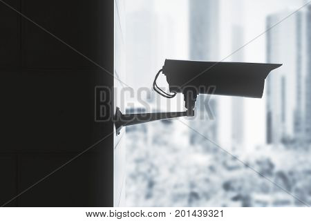 Side view of backlit CCTV camera on blurry city background. Privacy concept. 3D Rendering