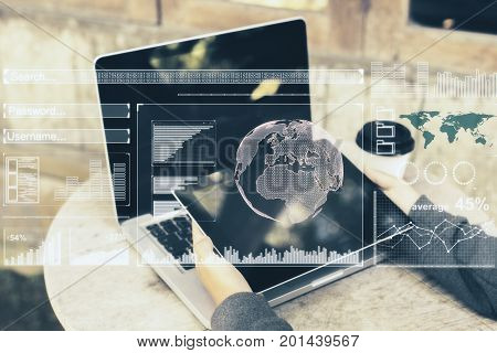 Side view of man hands using laptop and tablet with digital business hologram placed on wooden cafe table with coffee cup. Freelance and analytics concept. Double exposure