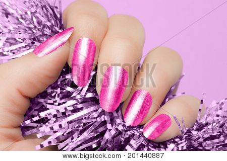 Female hand with pink nails hold purple textured decoration on purple background. Manicure concept.