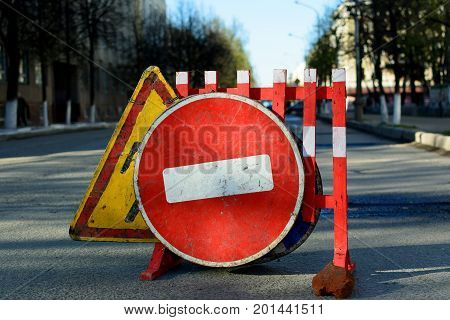 Photo of an old road stop sign standing on the road and road sign repair work