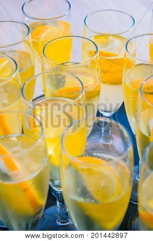 Champagne glasses on a tray with prosecco and orange slices in the sunlight