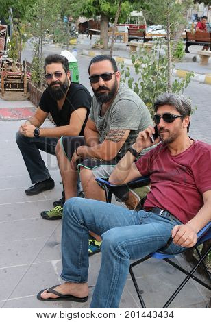 24TH JULY 2017, CAPPADOCIA,GOREME,TURKEY: Three bearded Turkish males sitting along the sidewalk in Goreme, turkey, 24th july 2017