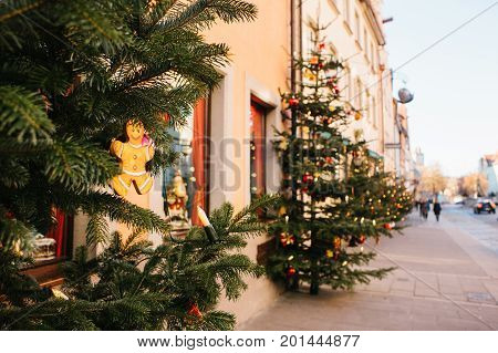 Decorated Christmas trees on the street in Rothenburg ob der Tauber in Germany. Selective focus on a Christmas toy on a branch. New Year's decor.