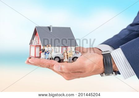 Insurance house car and family health live concept. The insurance agent presents the toys that symbolize the coverage.