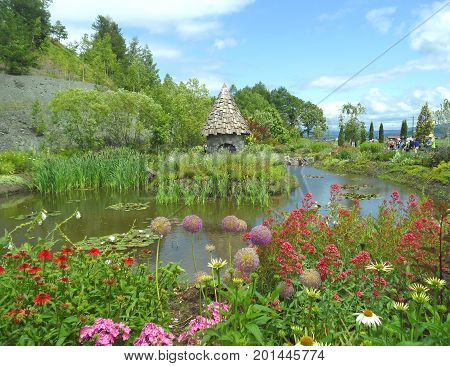 English country style garden with a fairy cottage on the pond