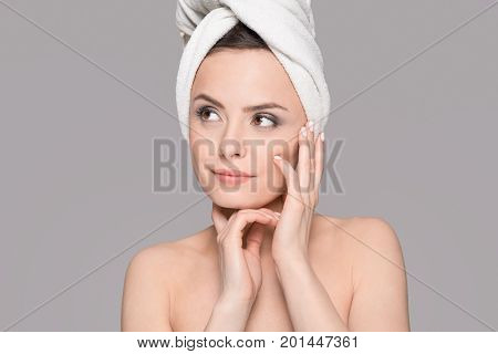 Perfect portrait of a young beautiful woman. Excellent skin and complexion. Copy space on a gray background. Topics of beauty and spa.