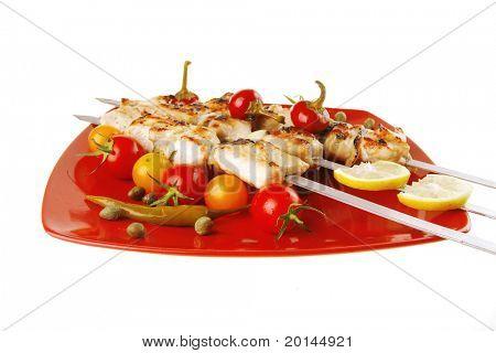 fresh grilled  pork shish kebab on red platter