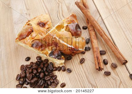 sweet food : apple pie cuts served on wooden plate over table with cinnamon and coffee beans