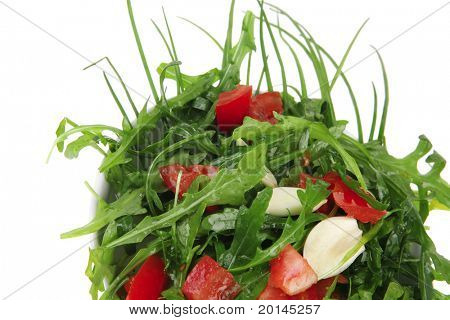 healthy food : salad with raw tomato , garlic , and green staff in white bowl isolated over white background