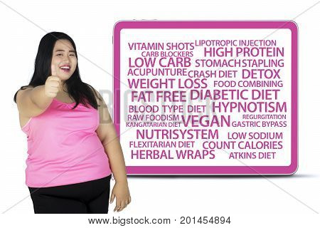 Fat woman showing thumb up while standing in the studio with diet methods on the billboard