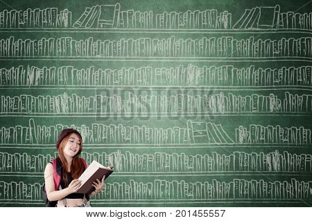 Image of female high school student reading a book while standing with a bookshelf on the chalkboard