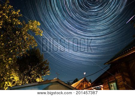 Starry sky with star trails over the wooden buildings