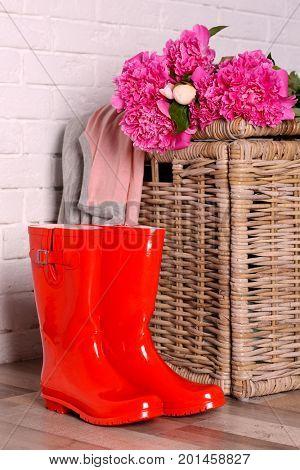 Red wellington boots on floor near brick wall
