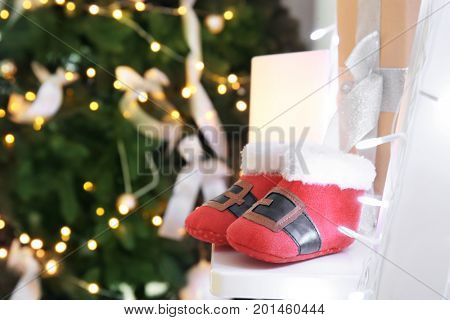 Cute booties for baby on step ladder in decorated room for Christmas