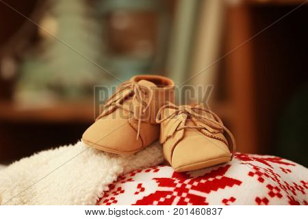 Baby booties on blurred background. Christmas concept
