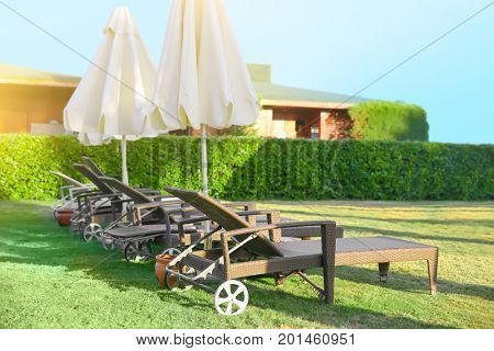 Comfortable sun loungers outdoors at resort