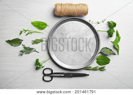 Composition with fresh herbs and metal plate on wooden background