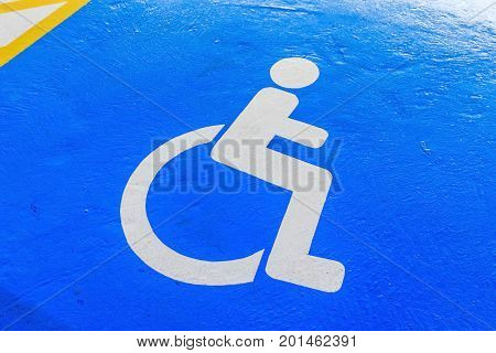 Handicap symbol on road traffic and pedestrians on parking space