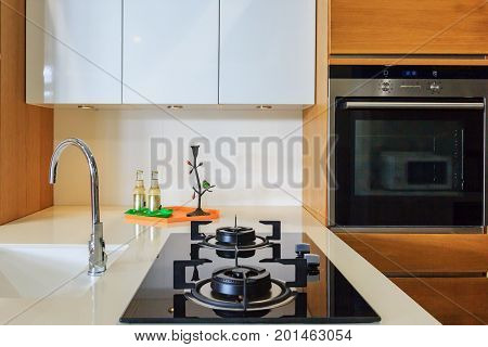 Modern kitchen interior with gas stove faucet sink and built-in electric oven in house.