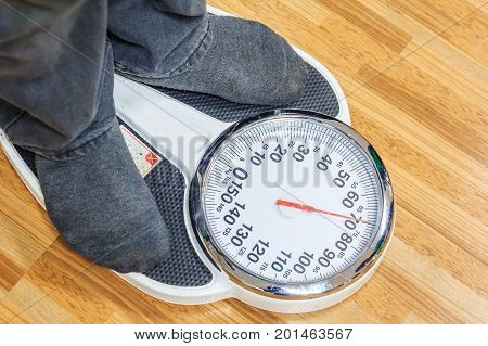 People are weighting on weight scales before annual physical examination. Weight Scales displaying numbers. Digital weight scales on wood background.Close up of people are using digital weight scales.